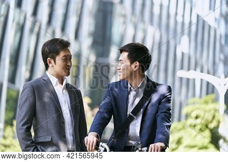 Two Asian Business Associates Having A Conversation In Downtown Of Modern City