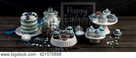 Delicious Cake And Cupcakes In Blue On Wooden Background. Table Setting For Celebration.