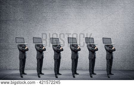 Businessmen In Suits With Laptops Instead Of Their Heads Keeping Arms Crossed While Standing In A Ro