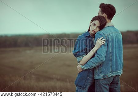 Denim style. Dramatic couple of young people in denim clothes standing in a valley hugging against a stormy sky. Beauty, fashion. Relationships.