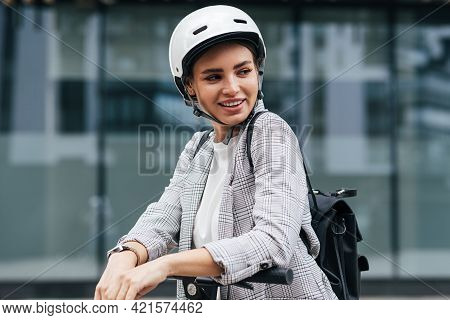 Young Businesswoman With Electric Scooter Looking Away. Cheerful Female In Safety Helmet Wearing Bac