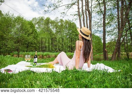 Young beautiful brunette woman in a dress is resting on the lawn in a summer park