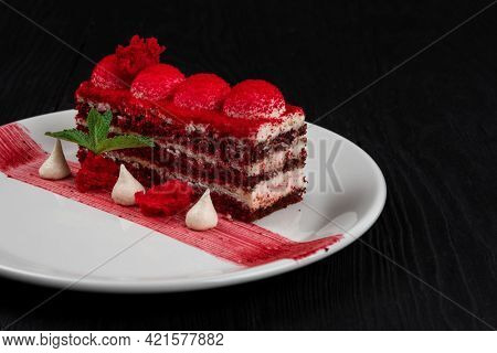 Plate with piece of delicious red velvet cake on black wooden background, food and drink concept