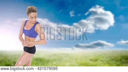 Composition of strong caucasian woman flexing biceps with copy space over clouds and blue sky. sport, fitness and active lifestyle concept digitally generated image.