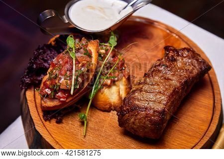 Grilled Veal Steak With Tomato Salsa On A Wooden Plate. Close-up, Selective Focus
