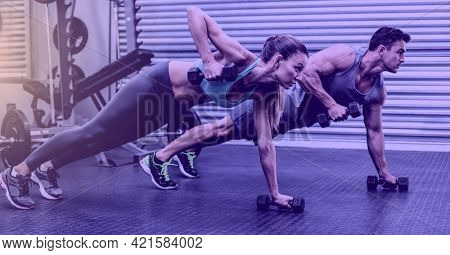 Composition of fit man and woman exercising with dumbbells over light blur. sport, fitness and active lifestyle concept digitally generated image.
