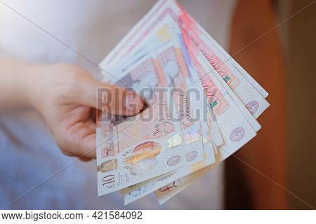 New Plastic Ten And Twenty Pound Note Sterling In Woman Hands. Crisis And Saving Concept. British Fi