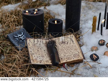 Open Book Of Spell With Black Candles And Runes In Snow.  Esoteric, Gothic And Occult Background, Ha