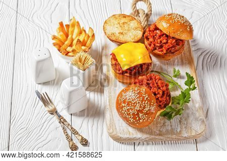 Sloppy Joe Sandwiches On Brioche Buns Served With French Fries On A White Wooden Board, Close-up, Am