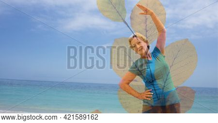 Composition of senior woman exercising on beach and autumn foliage. healthy active retirement lifestyle concept digitally generated image.