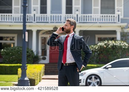 Business Man Holding Mobile Cell Phone Using App Texting Sms Message Wearing Suit. Young Urban Profe