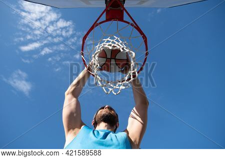Close Up Image Of Professional Basketball Player Making Slam Dunk During Basketball Game In Outdoor