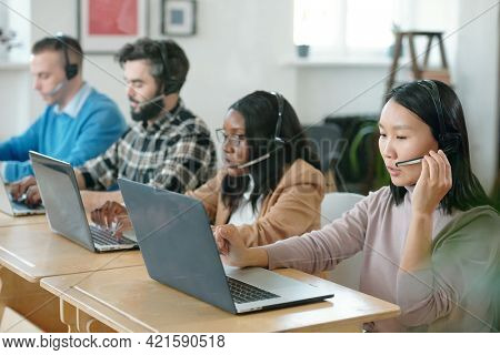 Group of serious young multi-ethnic customer service specialists using headsets with microphones and laptops while processing applications