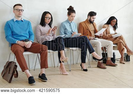 Group of serious young multi-ethnic job applicants in smart casual outfits sitting on chairs in line and preparing for interview in corridor