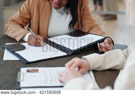 Close-up of black woman in jacket sitting at table and signing contract with company after job interview