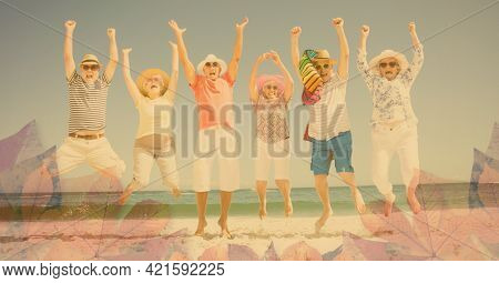 Composition of happy senior holiday group jumping raising hands, smiling on beach and autumn foliage. healthy active retirement lifestyle concept digitally generated image.
