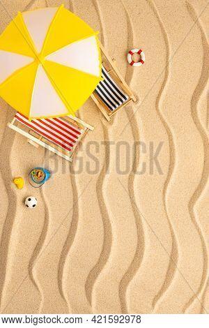 Summer beach concept. Sun loungers, sun umbrella and beach toys on yellow wave sand. Top view of beach.