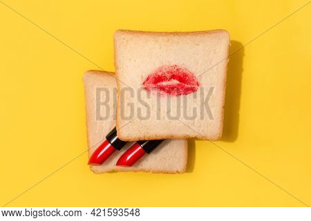 Creative Minimal Concept Made With Red Lipstick And Lips On Bread On Bright Yellow Background. Abstr