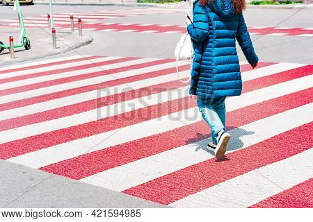 Woman Pedestrian Crossing The Street On A Crosswalk From Red And White Lines. Modern. Transportation