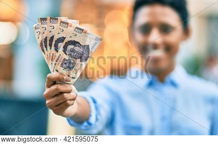 Young african american girl smiling happy holding mexican 500 pesos banknotes at the city.