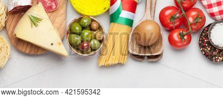 Italian cuisine food ingredients. Pasta, cheese, salami, olives and tomatoes. Top view flat lay