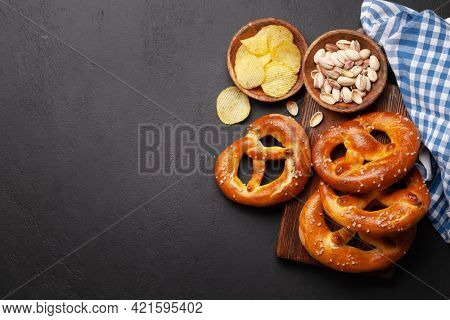 Potato chips, pistachio nuts and fresh baked homemade pretzel with sea salt on stone table. Classic beer snack. Top view flat lay with copy space
