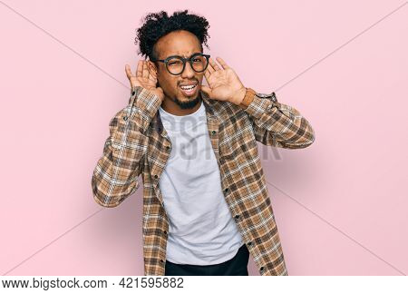Young african american man with beard wearing casual clothes and glasses trying to hear both hands on ear gesture, curious for gossip. hearing problem, deaf