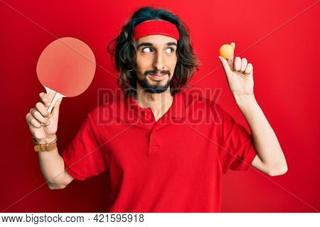 Young hispanic man holding red ping pong racket and ball smiling looking to the side and staring away thinking.