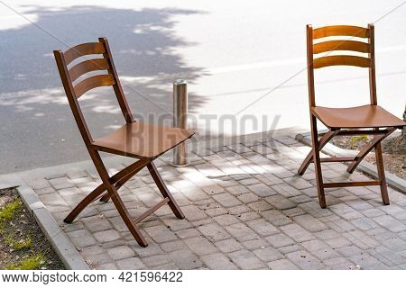 Two Empty Wooden Chairs Stands On The Street. Road. Pavement. Sidewalk. Restaurant. No People. City.