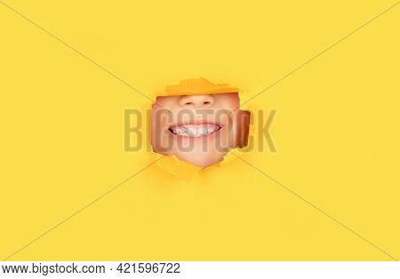 Positive Child With Toothy Pleasant Smile On Face, Keeps Through Torn Hole In Yellow Paper. Breaking
