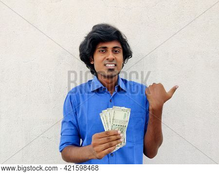 Clean Shaved Young Handsome Man Wearing Blue Shirt Holding Four 500 Rupees Notes And Pointing With T