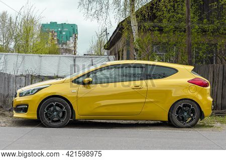 Yellow Coupe Car Against The Background Of An Old Wooden House. Day In City, Horizontal Shot Side Vi