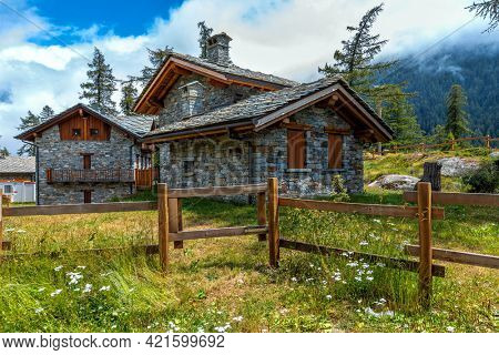 Stone guest houses and wooden fence on green meadow in the mountains in Piedmont, Northern Italy.