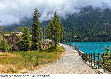 Narrow pathway along Lago di Ceresole and green trees in Piedmont, Northern Italy.