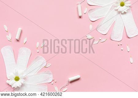 Menstrual Pads And Tampons With White Flowers Pink Background. Concept Woman Critical Days, Menstrua