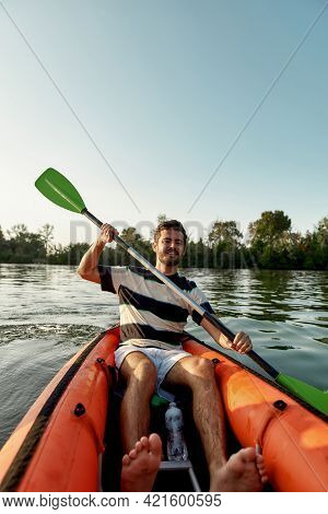 Active Young Man Looking Cheerful While Kayaking In A Lake, Surrounded By Peaceful Nature On A Summe