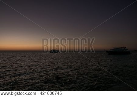 Red Sunrise Sky At Sea And Silhouettes Of Ships Sailing On The Sea.  Sunrise Over The Sea. Beautiful