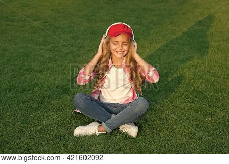 Relaxing Sound. Happy Child Listen To Sound Track Outdoors. Small Girl Enjoy Music Playing In Earpho