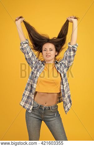 Sexy Woman With Fashion Look In Casual Style Hold Long Healthy Hair Yellow Background, Haircare