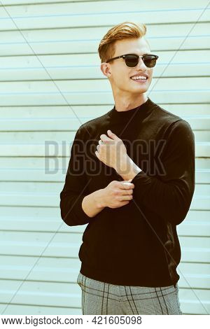 Portrait of a handsome positive young man in black pullover and sunglasses standing outdoor and smiling. Happy people concept.