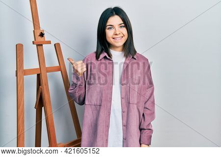 Young brunette woman standing by empty easel stand smiling happy pointing with hand and finger