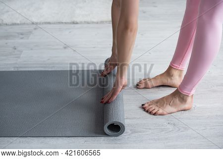 Cropped View Of Barefoot Woman Unrolling Yoga Mat At Home.
