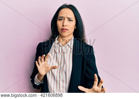 Young hispanic girl wearing business clothes disgusted expression, displeased and fearful doing disgust face because aversion reaction. with hands raised