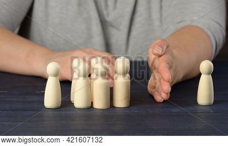 Female Hand Between Wooden Figures Of Men On A Blue Background. The Concept Of A Quarrel, Disagreeme