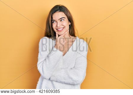 Young caucasian girl wearing casual clothes with hand on chin thinking about question, pensive expression. smiling with thoughtful face. doubt concept.