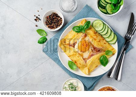 Egg, Ham And Cheese Are Wrapped And Fried In A Pancake And Decorated With Basil And Fresh Cucumber O