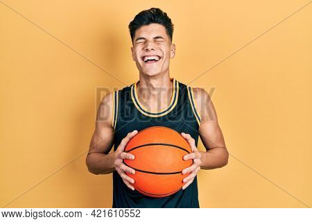 Young hispanic man holding basketball ball smiling and laughing hard out loud because funny crazy joke.