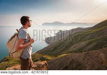 Young Man Travels Alone On The Backdrop Of The Mountains