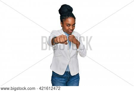 Young african american woman wearing business clothes punching fist to fight, aggressive and angry attack, threat and violence