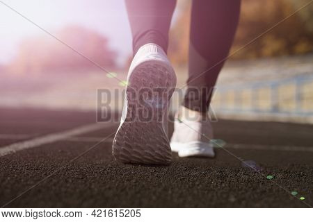 Healthy Lifestyle Is A Sport. Young Woman Runner Warming Up Before Run On City. Athlete Runner Feet